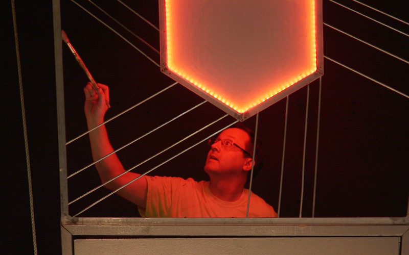 Man painting a theatre set washed in red lights