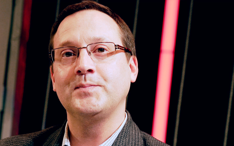 Portrait of a man wearing glasses with a red light in the background