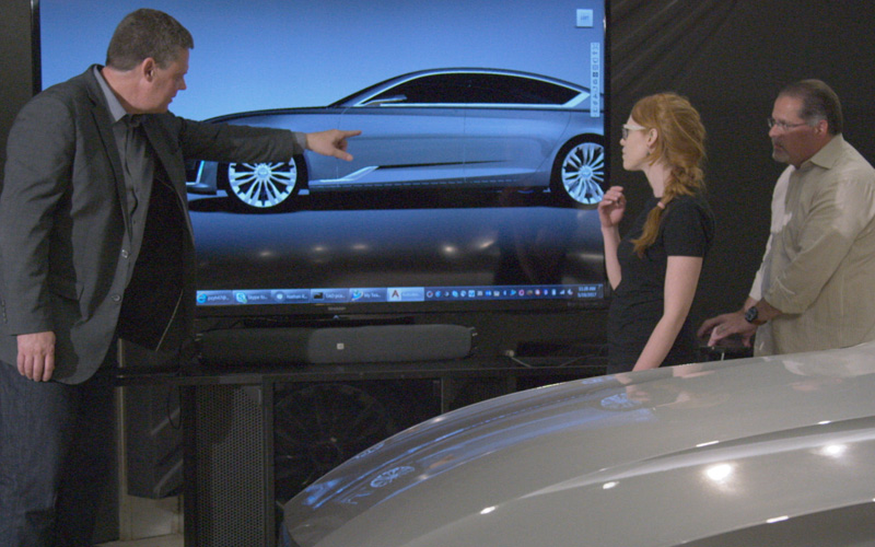 A man in a suit points to a screen showing a silver model of a car. A woman and another man stand to his right alongside the actual car