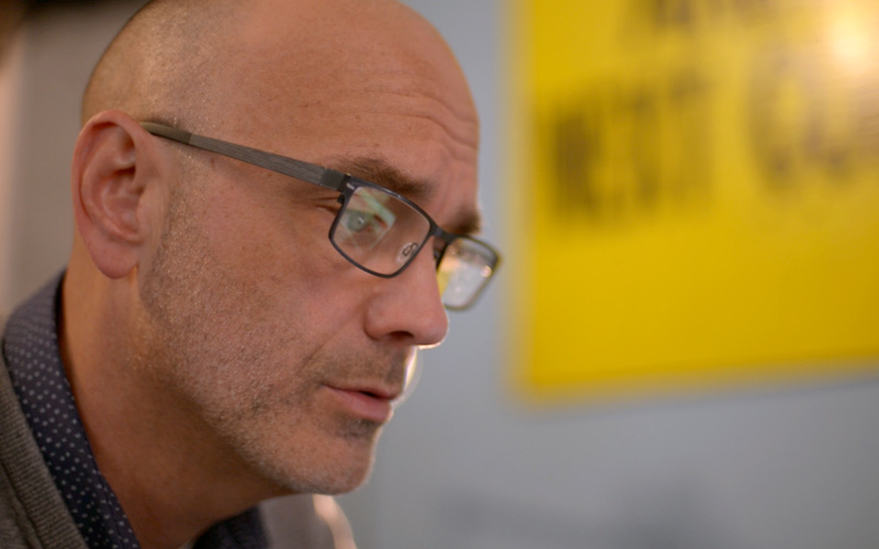 Profile portrait of a bald man with glasses sitting in front of a bright yellow sign