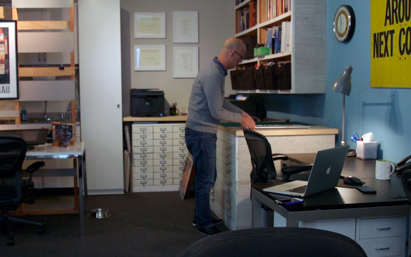 Bald man in gray sweater standing above file drawers and a work surface in a design studio