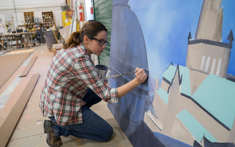 Gril wearing plaid shirt painting a backdrop for a theatre production inside of a large warehouse