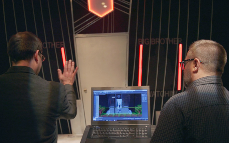 2 men with their backs to the viewer as the compare the computer model of a stage design and the actual stage.