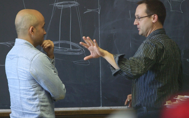 Two men standing in front of a chalkboard. One is explaining to the other what the circular drawing means.